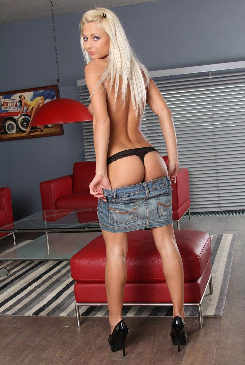 young blonde girl with a navel piercing undresses her black shirt, thongs and jean skirt in the living room with a red couch