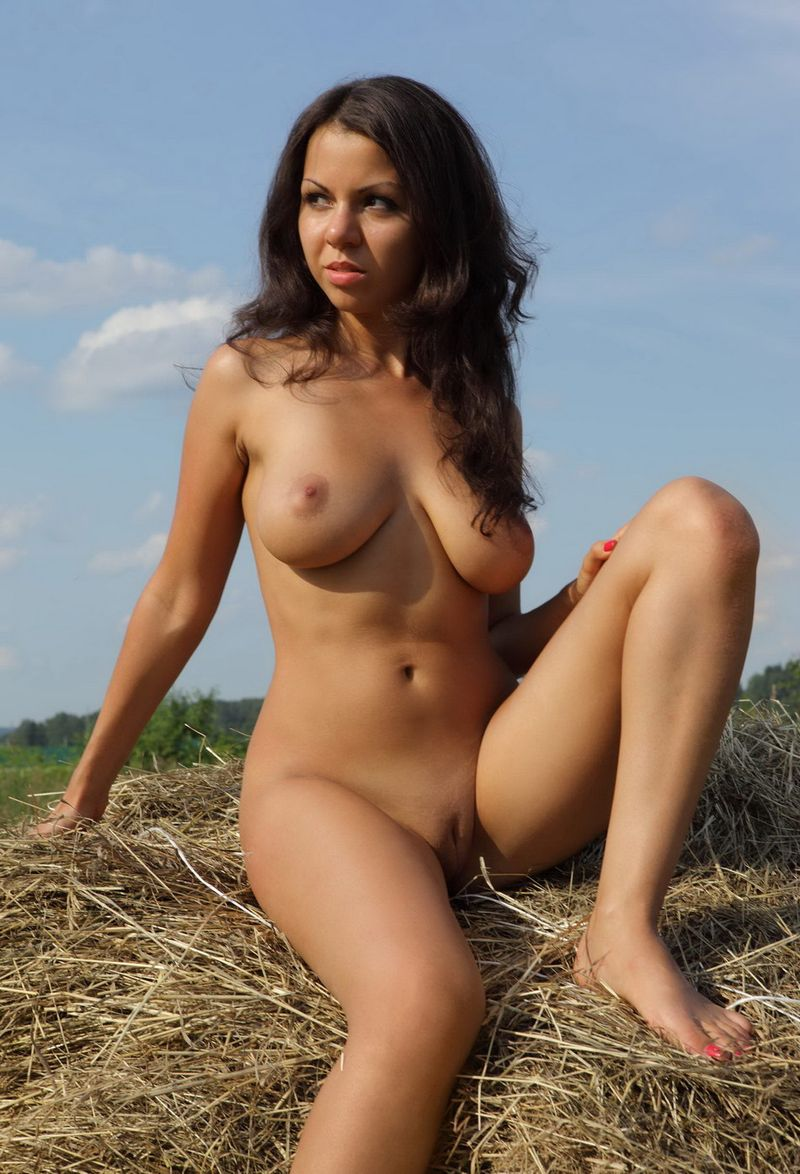 young brunette girl shows off her big natural breasts on the field with hay grass