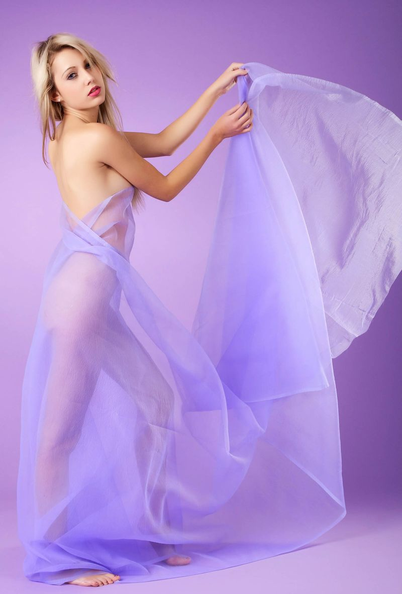 young blonde girl with blue eyes and flowers reveals her body in blue textile fabrics in the purple studio