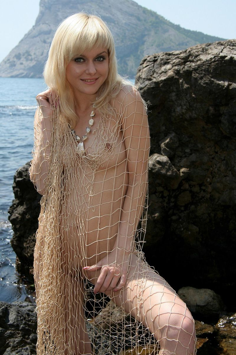 blonde girl reveals her shell necklace and fishing net on the rocky coast at the sea