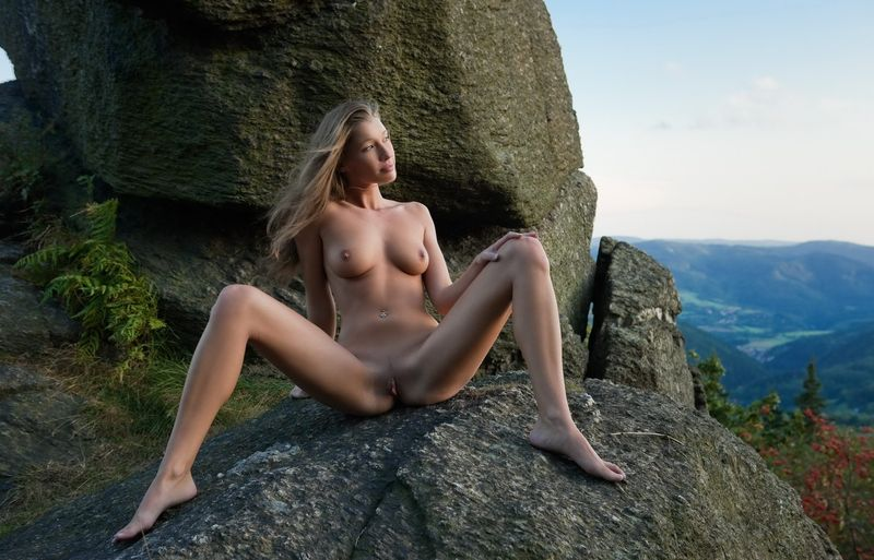 cute young blonde girl with a navel piercing posing naked on rocks in high mountains