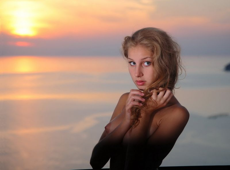cute young curly blonde girl with a necklace and pendant reveals her black chemise with stockings at home in the evening sunset
