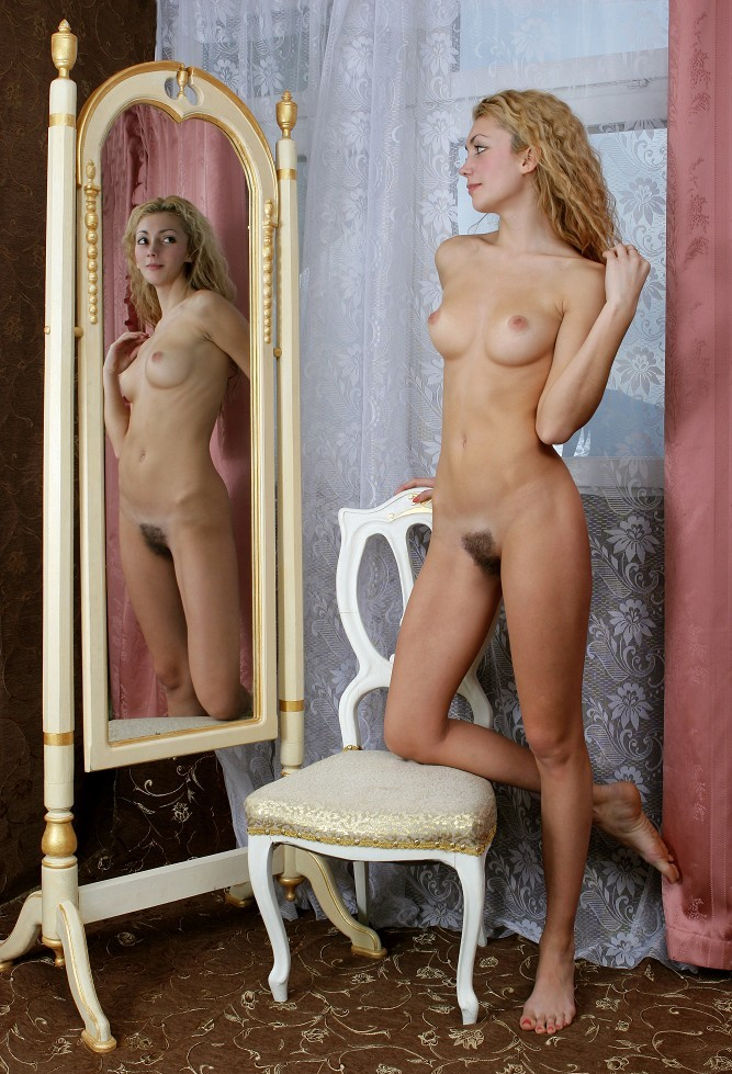 young curly blonde girl with natural untrimmed pubic hair posing on the chair at the mirror