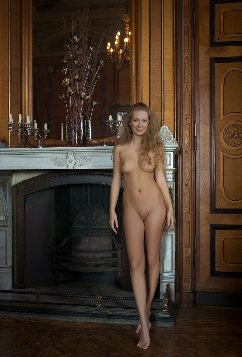 young curly blonde girl with long hair and blue eyes shows off in the hall with a fireplace