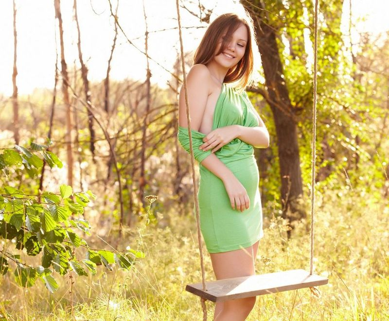 cute young brunette girl with blue eyes and full natural breasts strips her green dress outside on the wooden swing
