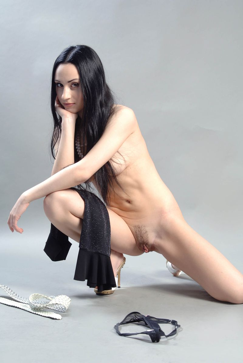 young black haired girl with a pearl necklace reveals her black dress and large labia minora in the studio