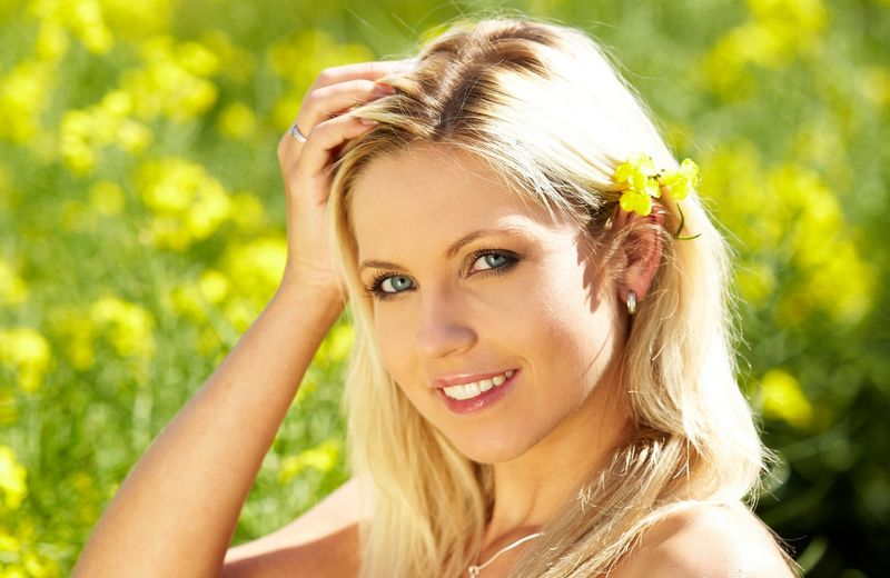 blonde girl with blue eyes shows off her necklace, pendant, navel piercing, blue scarf and white underwear on the field of wild yellow flowers