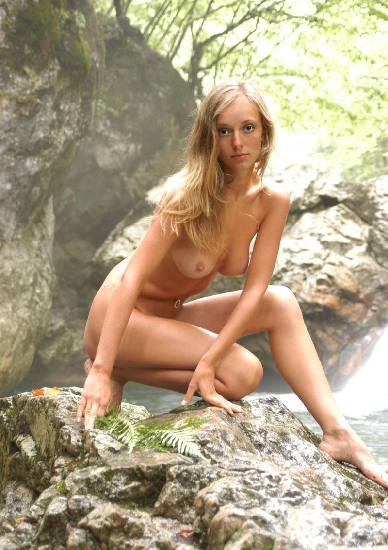 young blonde girl reveals her navel piercing in the nature on rocks at the small stream in the forest