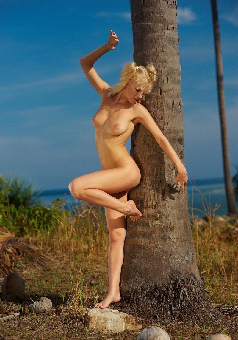 young blonde girl with pigtails posing among coconut palms near the sea