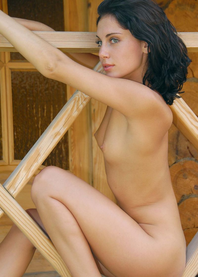 cute young black haired girl shows off on the wooden porch