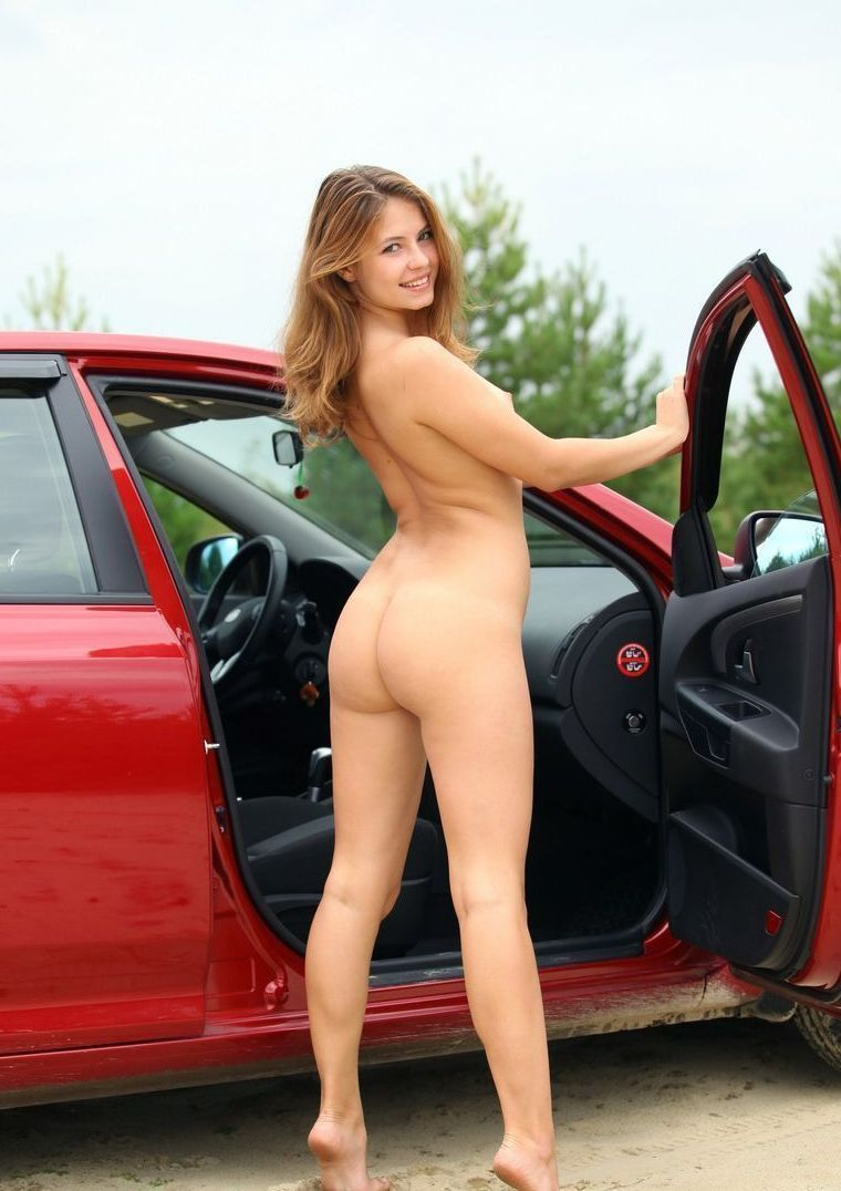 young brunette girl posing naked outside at the red car