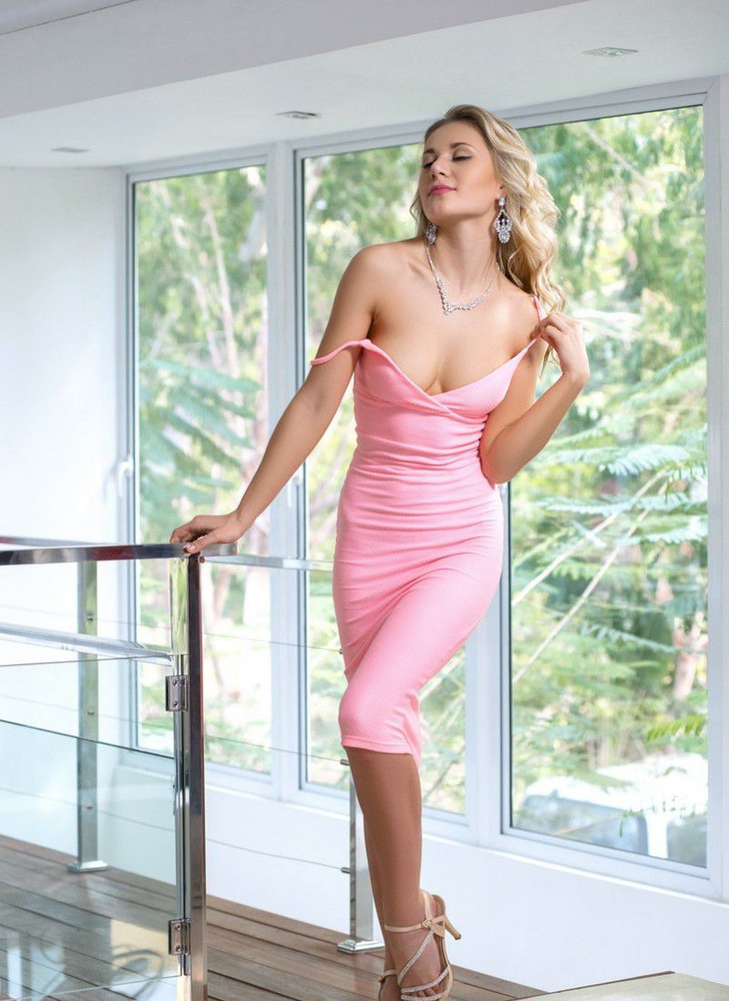 young curly blonde girl with a navel piercing undresses her pink dress at the window