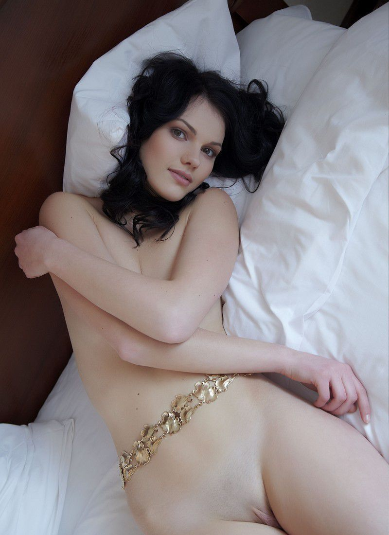 young curly black haired girl with a golden belt shows off on the bed