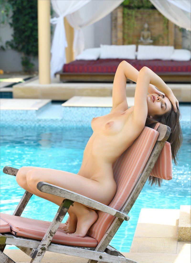 young brunette girl undresses her swimsuit on the deckchair at the swimming pool