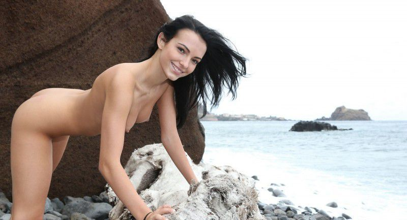 young black haired girl reveals her short jeans on the driftwood on the rocky shore at the sea