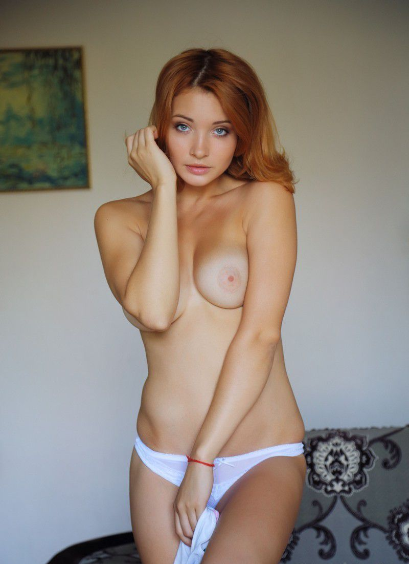 young red haired girl with blue eyes reveals her underwear on the couch at home