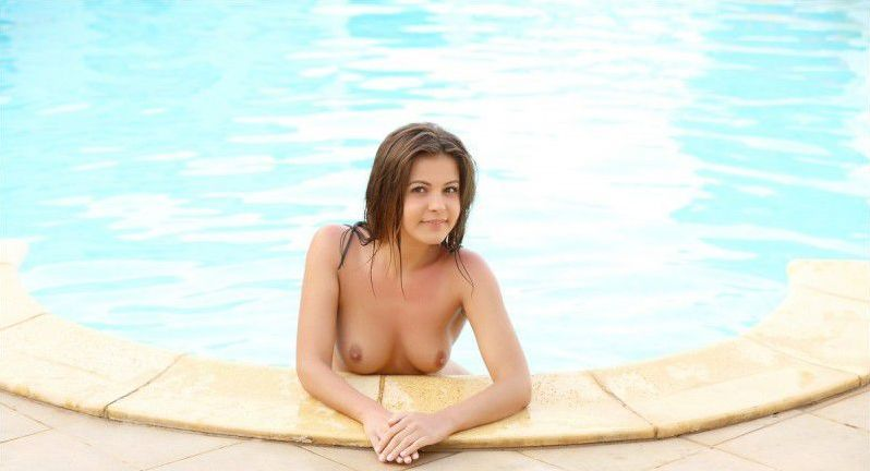 cute young brunette girl undresses her blue bikini at the swimming pool