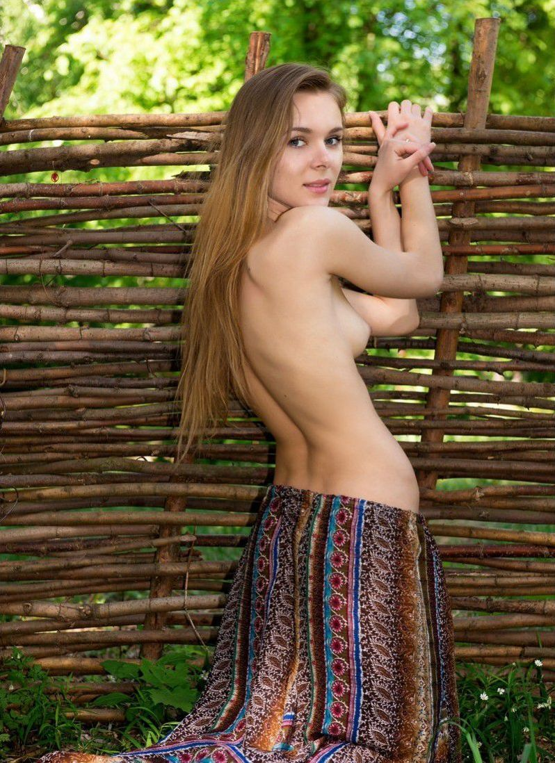 young dark blonde girl reveals her dress near the wooden fence