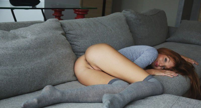 young red haired girl with blue eyes reveals her bodysuit and knee high socks on the couch