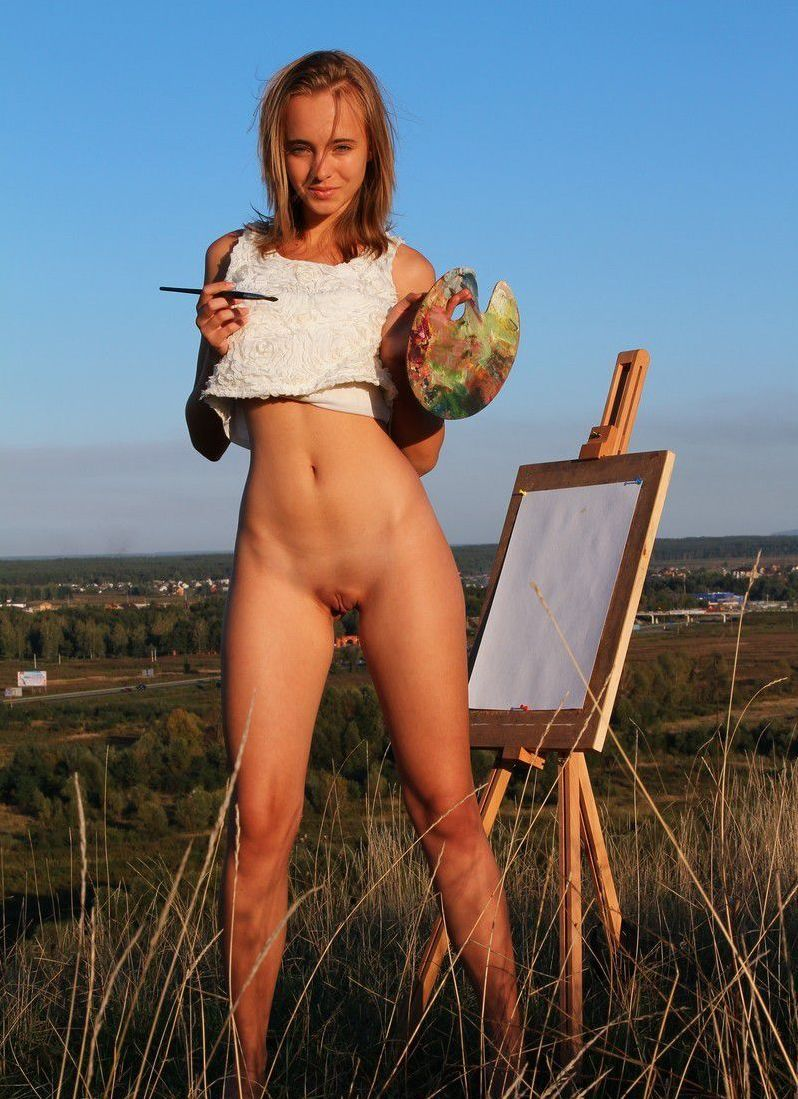cute young blonde girl painting a picture outside in a white sleeveless top
