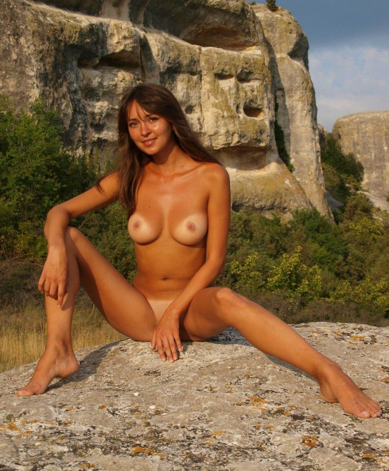 young brunette girl shows off her tan lines outside on rocky mountains