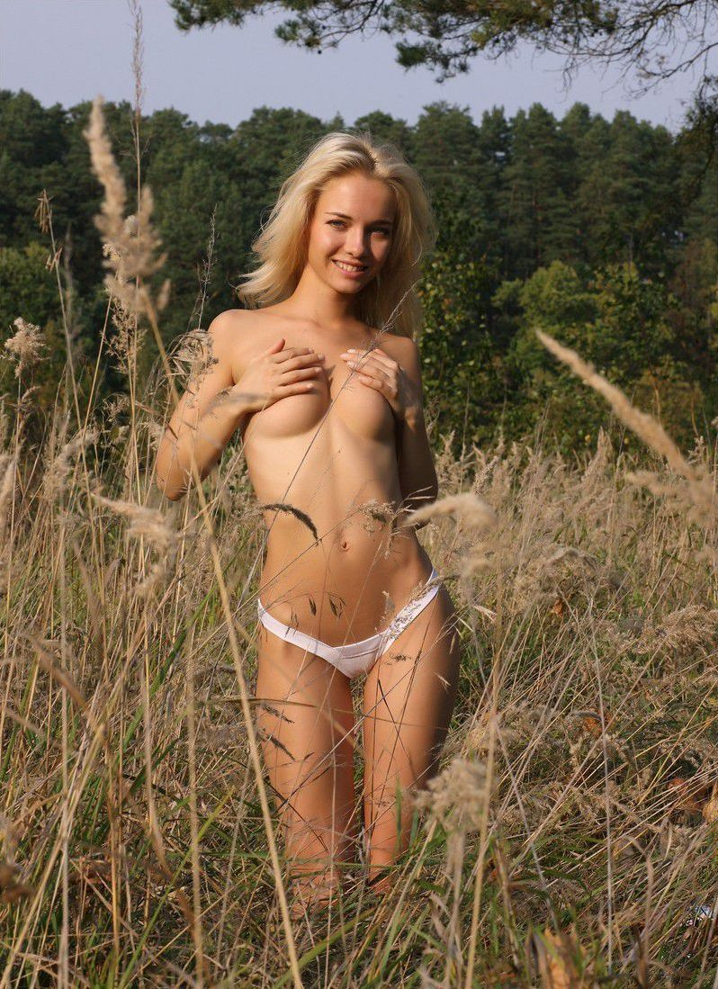 cute young blonde girl reveals her white gee string panties outside on the glade field in the nature