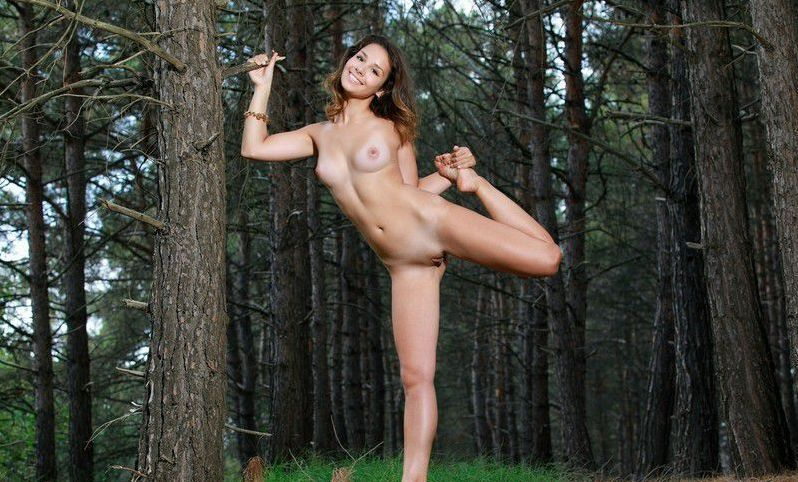 young brunette girl with a bracelet reveals her dress in the dark forest