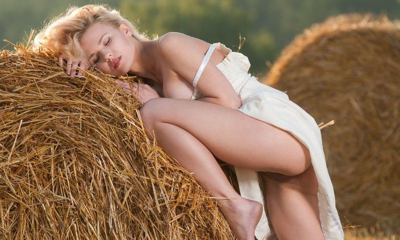 curly blonde girl reveals her white underskirt on the field with a hay grass