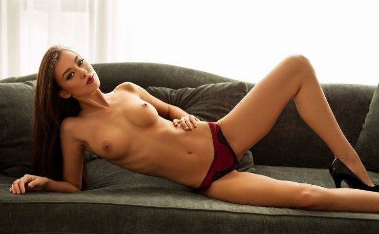 young brunette girl reveals her red and black lingerie and high heels on the couch