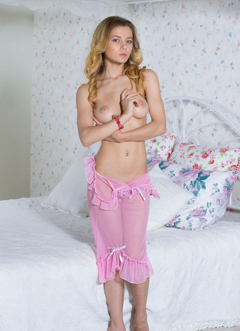 young curly blonde girl with a red bracelet reveals her pink satin negligee in the bed at home