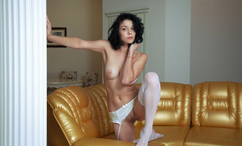 curly black haired girl with blue eyes reveals her white hold-ups with garter belts suspenders on the couch