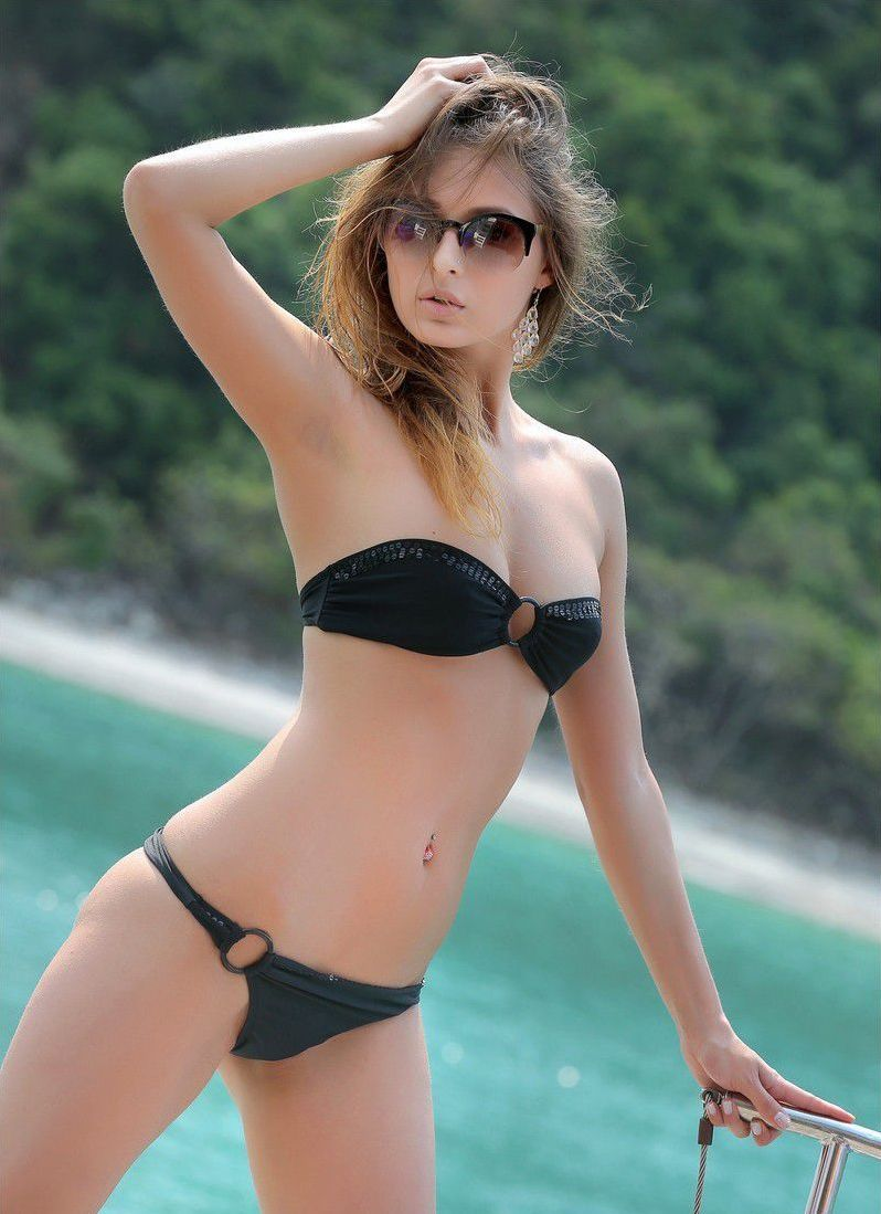 young brunette girl with a navel piercing, earrings and sunglasses reveals her black bikini at the sea