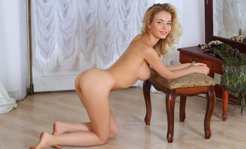 young curly blonde girl reveals her dress with necklaces on the footstool at home