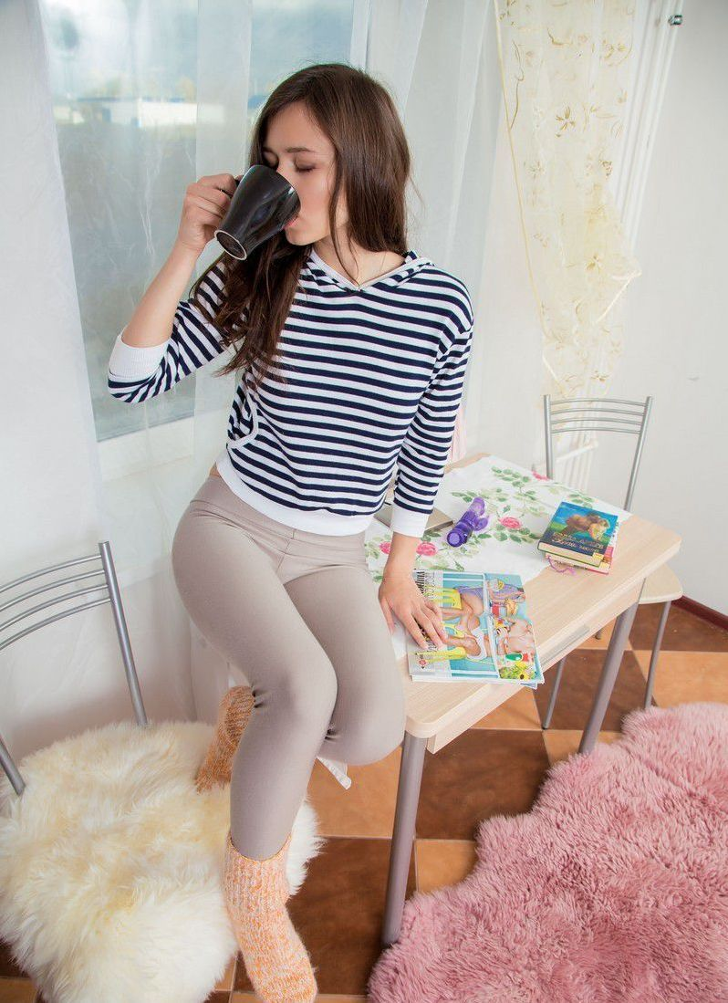 cute young brunette girl reveals her pullover and leggings on the fur carpet