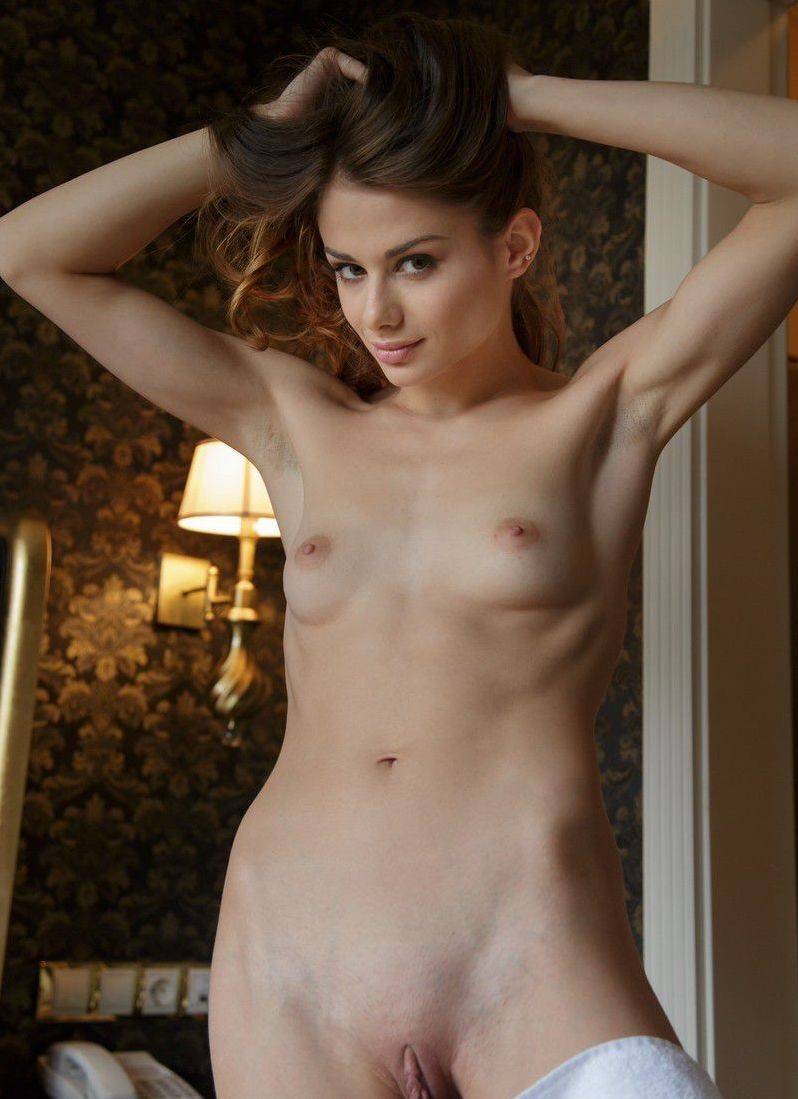 cute young brunette girl reveals her white towel in the hotel bedroom