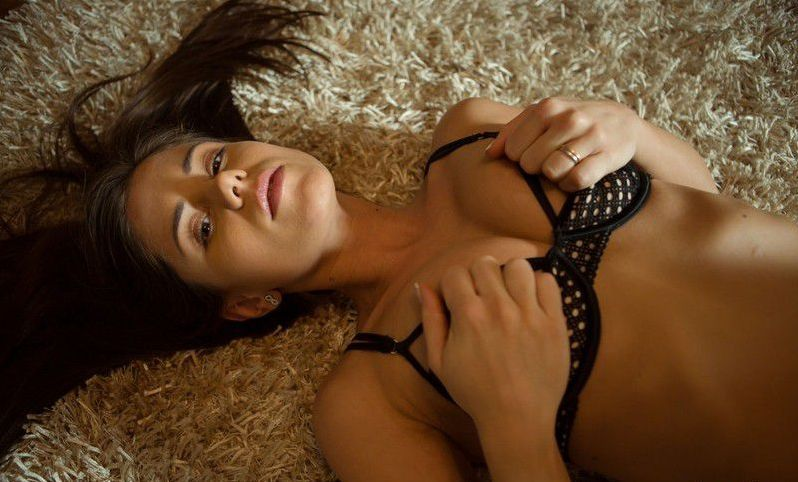 young brunette girl reveals her black stockings with garter belts suspenders on the fur carpet