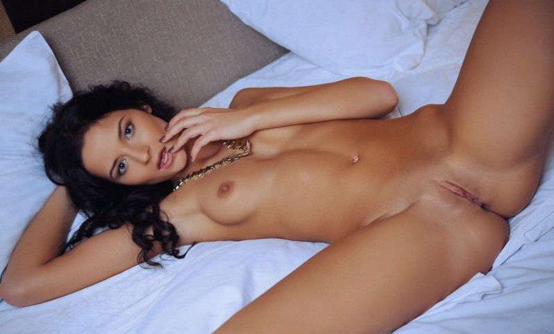 young curly black haired girl with a necklace and navel piercing reveals her pink knickers on the bed