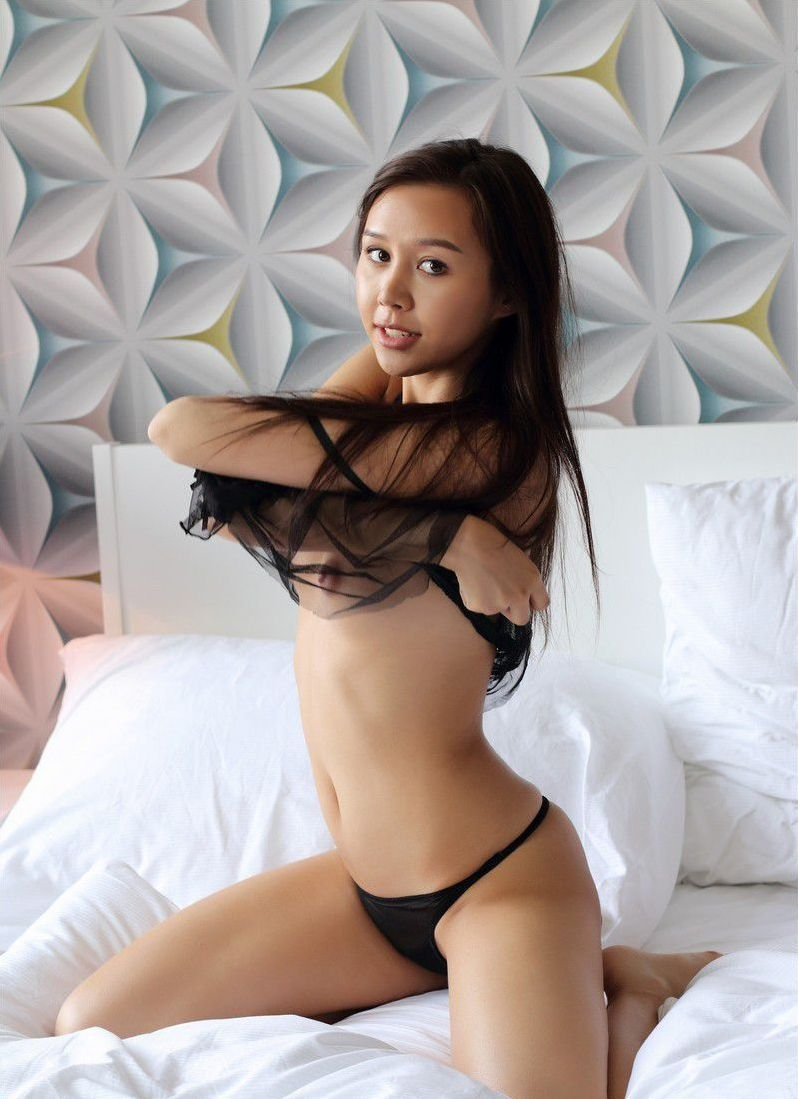 young asian girl with a pearl necklace reveals her black transparent chemise and panties on the bed