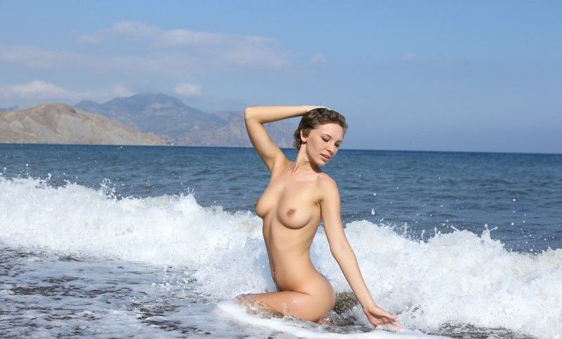 young dark blonde girl reveals her white sleeveless shirt on the rocky shore at the sea