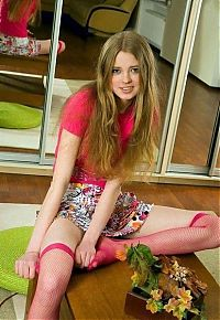 Babes: young golden blonde girl reveals her pink fishnet hold-ups at home