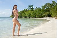 Babes: young brunette girl reveals her bikini on the beach at the sea