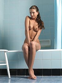 Babes: young brunette girl posing with a stool in the blue bathroom