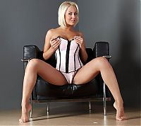 Nake.Me search results: blonde girl undresses her white corset on the black armchair