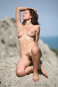 Babes: red haired girl reveals outside on the hill on rocks