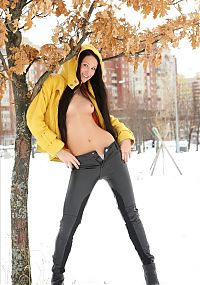 Babes: young brunette girl undresses a yellow coat and black leather pants outdoors in the winter