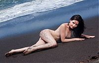Babes: brunette girl on the beach with black sand