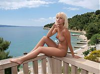 Babes: young blonde girl on the balcony with a sea view