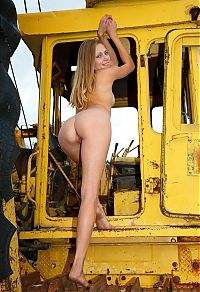 young blonde girl on the old yellow excavator
