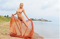 Babes: blonde girl with textile fabric at the lake with fortress