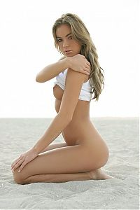 Babes: cute young blonde girl shows off her body in the sand